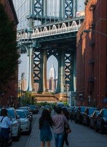 Zicht op Manhattan Bridge met doorkijk naar Empire State Building